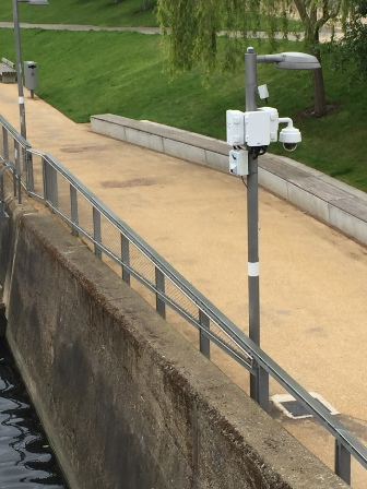 uma-caixa-branca-com-sensor-presa-a-um-candeeiro-na-beira-de-uma-ponte-do-jardim