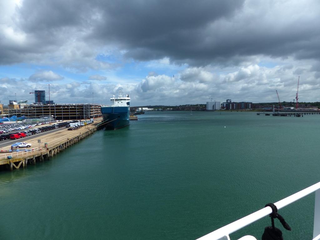 da-amurada-de-um-navio-observa-se-um-porto-com-um-navio-la-ao-fundo