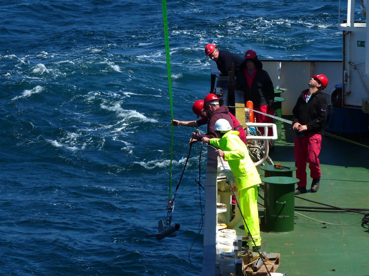 homens-com-capacete-a-bordo-de-um-navio-colocam-aparelho-na-agua-do-mar-com-ajuda-de-um-cabo