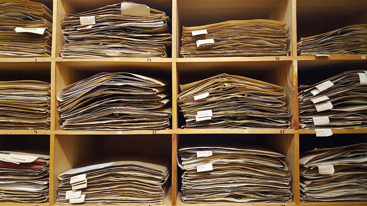 capas de papel empilhadas num armário de prateleiras
