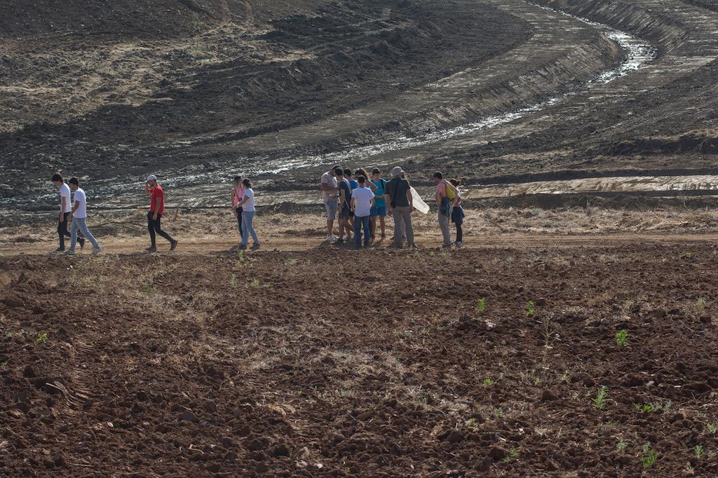 Grupo de alunos no meio de uma planície de terra castanha