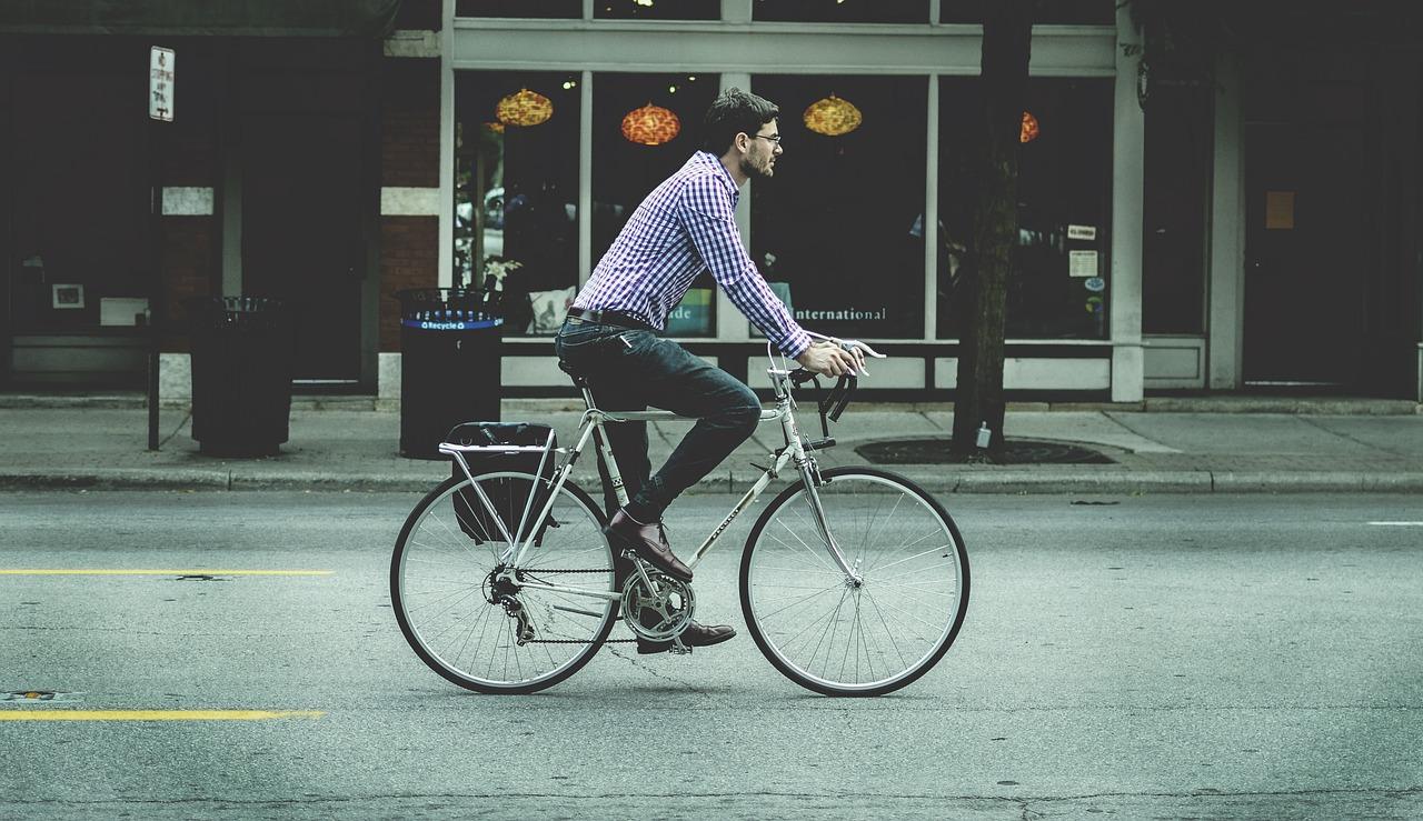 um homem a andar de bicicleta na cidade