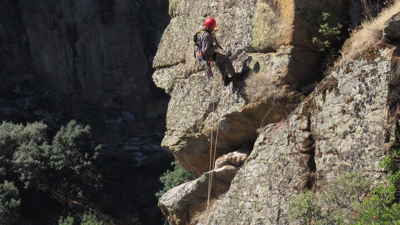 homem a descer arriba com equipamento de escalada